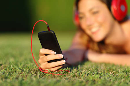 listening device: Close up of a woman with headphones holding a smart phone lying on the grass in a park or a garden