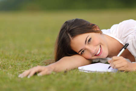 writing book: Happy woman lying on the grass and writing in a notebook with unfocused green background