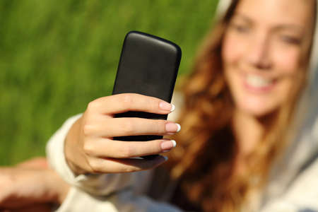 Teenager girl hand using a smart phone with her face and green nature in the background                  photo