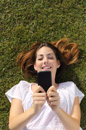 Top view of a happy woman with white dress lying on the grass texting on a smart phone