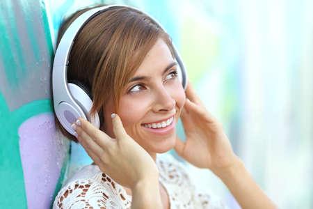 musica electronica: Mujer feliz con los auriculares escuchando la m�sica con una pared de graffiti borrosa en el fondo