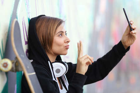 Skater teenager girl taking a photograph with smart phone camera with blurred graffiti wall in the background