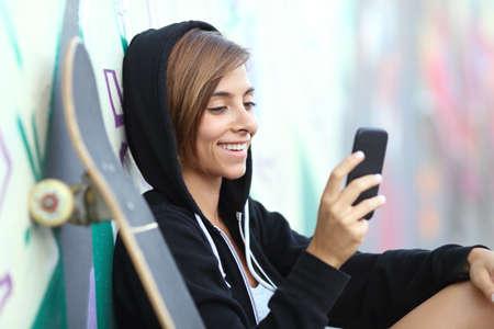 adolescente: Patinadora joven muchacha adolescente feliz usando un teléfono inteligente con una pared de graffiti borrosa en el fondo Foto de archivo