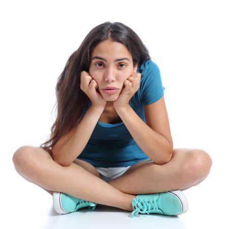 Chica adolescente aburrido que se sienta con las piernas cruzadas aislados sobre un fondo blanco