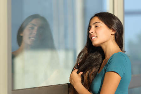 combing hair: Flirty teen girl combing her hair using a window like a mirror outdoor in the street