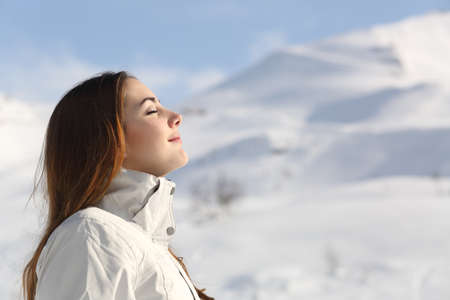 breath: Profile of an explorer woman breathing fresh air in winter with a snowy mountain in the background Stock Photo