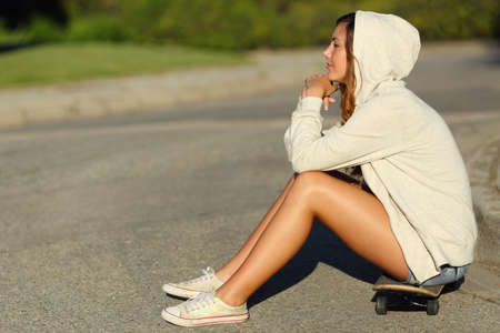 Full body of a profile of a pensive teenager girl sitting on a skate in the street looking away              photo