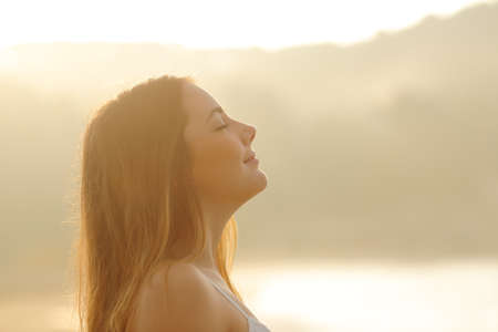Backlight profile of a woman breathing deep fresh air in the morning sunrise isolated in white above Stock Photo