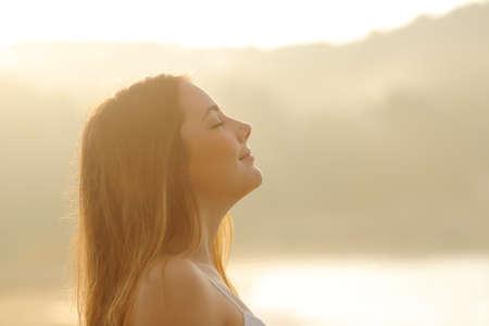 respiracion: Perfil contraluz de una mujer respirando aire fresco profundo en el amanecer de ma�ana aislado en blanco por encima de