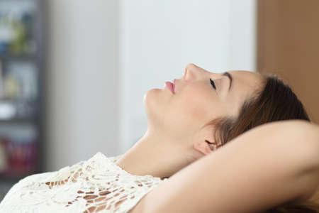リラックスして、自宅のソファで寝ている女性の側面図