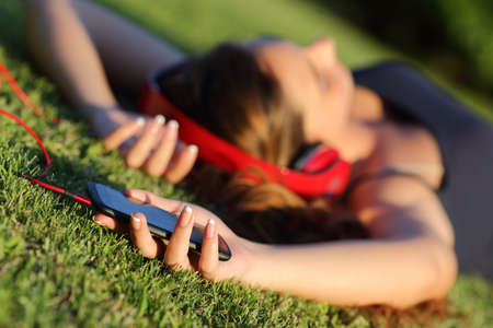 Girl listening music with headphones and holding a smart phone lying on the green grass in a park 스톡 콘텐츠