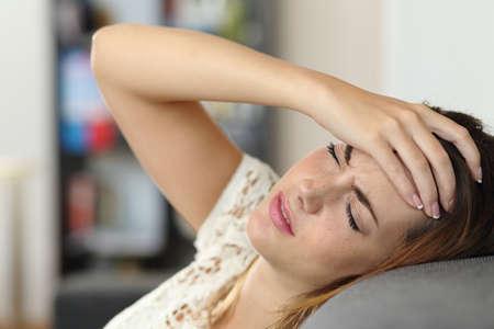 dolor de cabeza: Mujer Ama de casa en un sofá con dolor de cabeza y una mano en la frente