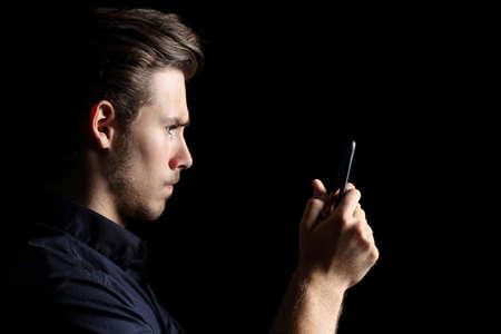 Geobsedeerd boos tiener texting op de slimme telefoon geïsoleerd op een zwarte achtergrond Stockfoto