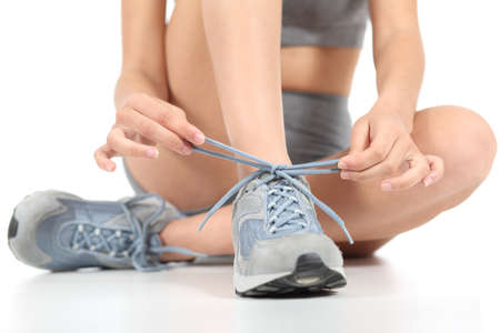 shoestrings: Runner fitness woman tying the shoelaces ready to sport isolated on a white background