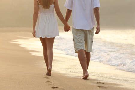 držení: Zadní pohled na pár na procházce se drží za ruce na pláži při východu slunce