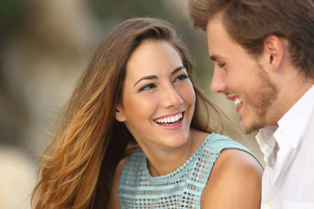 dating: Funny couple laughing with a white perfect smile and looking each other outdoors with unfocused background Stock Photo