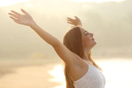 Relaxed donna respira aria fresca braccia sensibilizzazione al sorgere del sole con un calore sfondo dorato Archivio Fotografico
