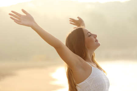 breath: Relaxed woman breathing fresh air raising arms at sunrise with a warmth golden background