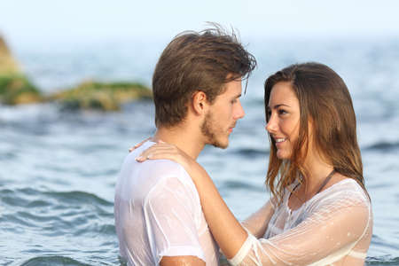 love at first sight: Profile of a young couple in love bathing in the sea in the beach