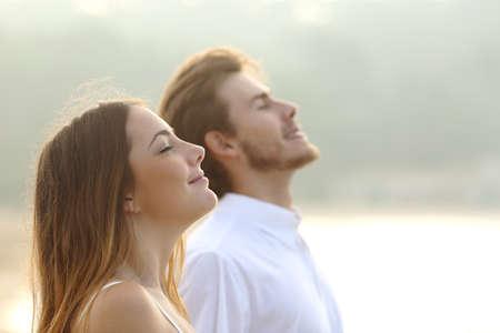 respiration: Profil d'un couple de l'homme et de la femme respirer de l'air frais profonde ensemble au coucher du soleil