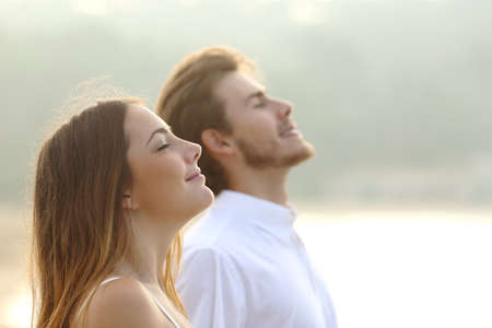 and the air: Profile of a couple of man and woman breathing deep fresh air together at sunset                Stock Photo