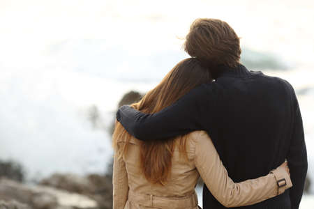 Achter mening van een paar knuffelen in de winter geïsoleerd in het wit boven Stockfoto