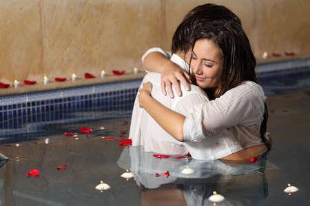 mojar: Abrazos pareja rom�ntica en una piscina con velas y p�talos de rosa flotando en el agua de rosas Foto de archivo