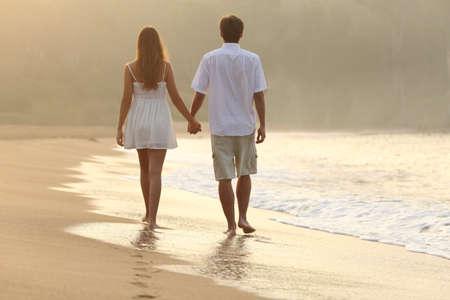 siluetas de enamorados: Vista posterior de una pareja caminando y tomados de la mano en la arena de una playa al atardecer Foto de archivo