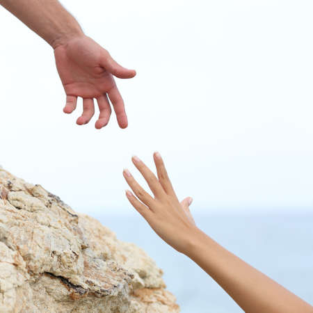 Man and woman hands helping concept with the sea in the background 写真素材