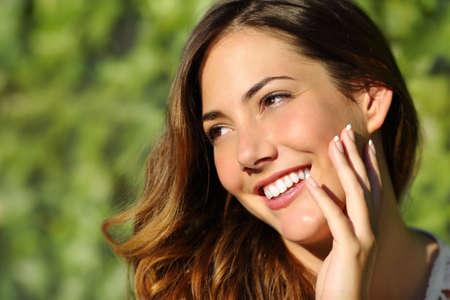 Schoonheid vrouw met een perfecte glimlach en witte tand met een groene achtergrond Stockfoto