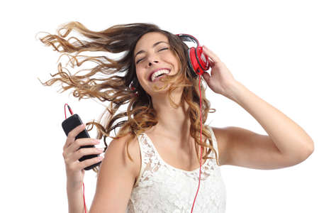 listening device: Happy girl dancing and listening to the music isolated on a white background Stock Photo
