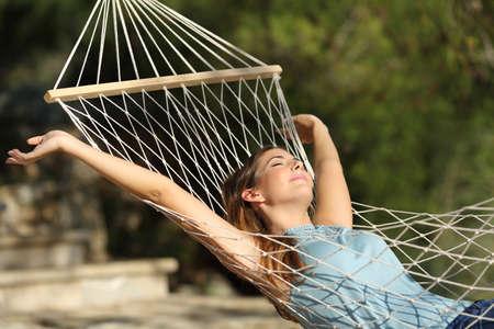descansando: Mujer feliz que se relaja en una hamaca en vacaciones y levantar los brazos en la montaña