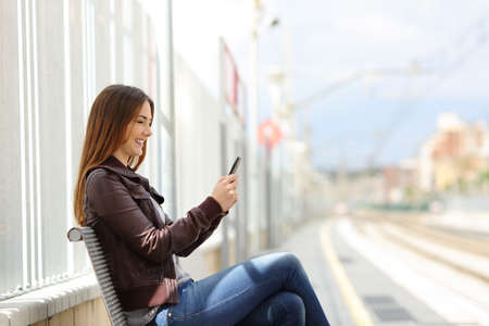 Happy woman texting on a smart phone in the train station with the railway in the background