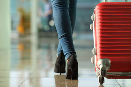 carry: Traveler woman legs walking carrying a suitcase in an airport