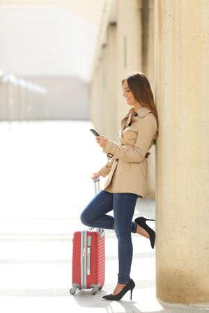 gente aeropuerto: Mujer de mensajes de texto de los viajeros de un teléfono inteligente mientras está esperando con una maleta en un aeropuerto o una estación