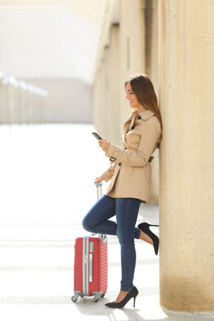 travel luggage: Traveler woman texting a smartphone while is waiting with a suitcase in an airport or a station