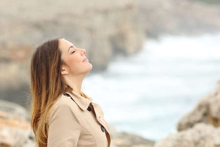 exercises: Woman breathing fresh air in winter on the beach with the sea in the background