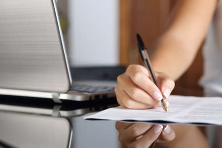 Close up of a woman hand writing a contract with a laptop beside at home or office photo