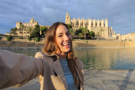 Tourist woman photographing a selfie in Palma de Mallorca Cathedral on holidays