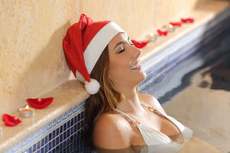 Woman relaxing in a spa on christmas holidays wearing a santa claus cap photo