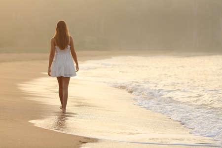 夕暮れ時のビーチの砂の上を歩いて女性の背面図