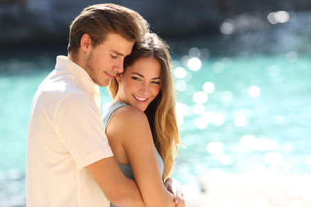 dattes: Couple amoureux �treindre sur une plage tropicale avec une eau turquoise � l'arri�re-plan