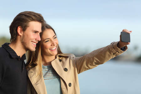 taking photograph: Happy couple photographing a selfie with the smart phone outdoors in winter