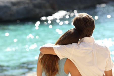 Couple hugging and watching the turquoise sea on holidays in a tropical beach