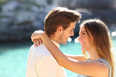Couple in vacations looking each other ready to kiss with a turquoise water in the background