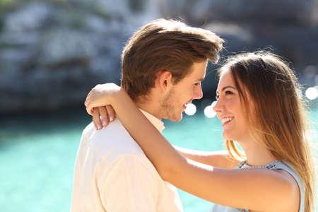 Paar in vakanties op zoek elkaar klaar te kussen met een turquoise water op de achtergrond Stockfoto