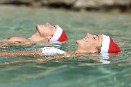 Couple swimming on a tropical beach on christmas holidays in a clean transparent sea water