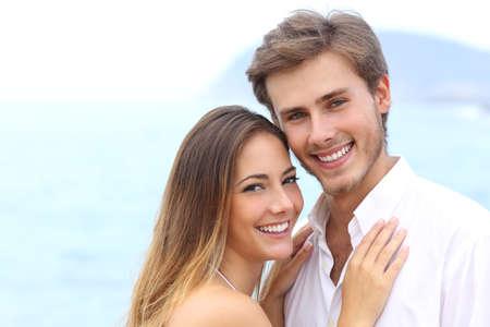 Gelukkig paar met een witte glimlach te kijken naar de camera op vakantie op het strand op een witte boven
