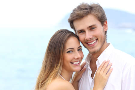 young man smiling: Happy couple with a white smile looking at camera on holidays on the beach isolated on white above