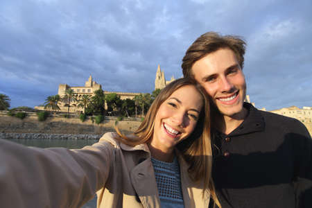 Tourist couple on holidays photographing a selfie with Palma de Mallorca Cathedral in the background